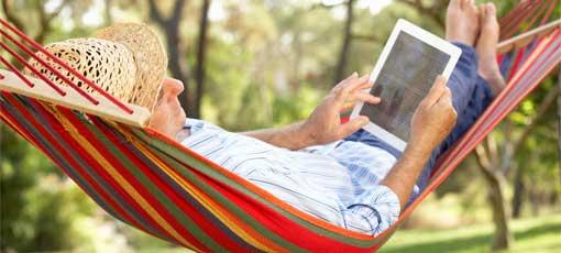 Ein Mann liegt in einer Hängematte und liest auf einem iPad