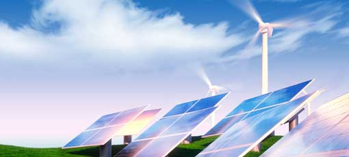 Photovoltaik-Anlagen stehen vor Windrädern auf einer Wiese